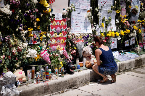 A woman kneels at a memorial site created by neighbors in front of a partially collapsed residential building on Sunday