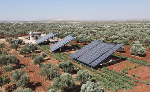 This aerial picture shows solar panels installed in agricultural fields, in the village of Killi, near Bab al-Hawa by the border with Turkey, in Syria's northwestern Idlib province, on June 9, 2021