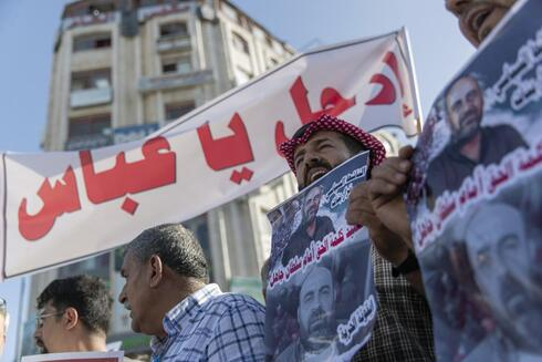 """Demonstrators carry posters with pictures of Palestinian Authority outspoken critic Nizar Banat that reads """"a Martyr of saying the truth in front of an ignorant Sultan,"""" and a banner that reads """"Abbas, leave,"""" during a rally protesting his death, in the West Bank city of Ramallah"""
