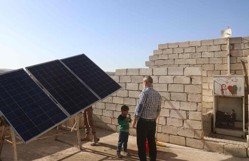 Zakariya Sinno and his son stand near a solar panel installed on the rooftop of his house in the village of Killi, near Bab al-Hawa by the border with Turkey, in Syria's northwestern Idlib province, on June 9, 2021