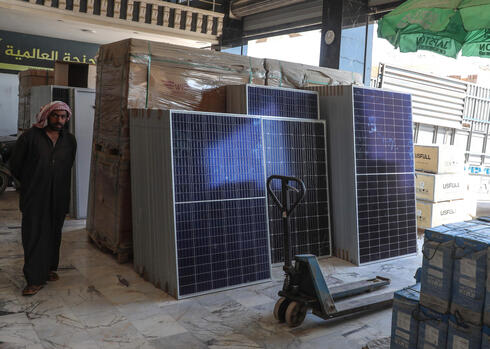 A man stands near solar panels displayed at a shop in the town of Dana, east of the Turkish-Syrian border in the northwestern Syrian Idlib province, on June 10, 2021