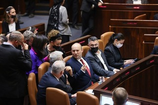 Prime Minister Naftali Bennett is flanked by members of his government in the Knesset plenum ahead of the vote on Monday night
