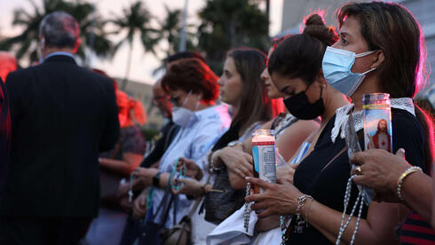 People gather at the memorial site for victims of the collapsed 12-story Champlain Towers South condo building to pray the rosary on July 07, 2021 in Surfside