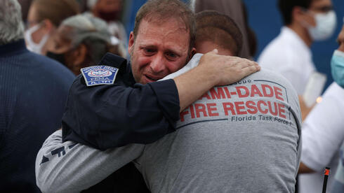 escue workers with the Miami Dade Fire Rescue embrace after a moment of silence near the memorial site for victims of the collapsed 12-story Champlain Towers South condo