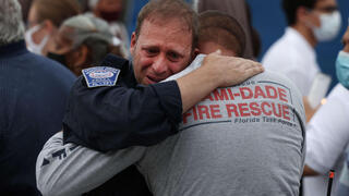 Rescue workers with the Miami Dade Fire Rescue embrace after a moment of silence near the memorial site for victims of the collapsed 12-story Champlain Towers South condo