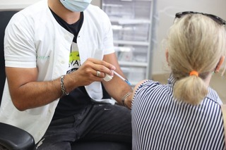 Health worker administers a COVID-19 vaccine to a woman in Tel Aviv