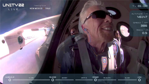 Billionaire Richard Branson smiles on board Virgin Galactic's passenger rocket plane VSS Unity before starting its untethered ascent to the edge of space above Spaceport America near Truth or Consequences, New Mexico, U.S. July 11, 2021