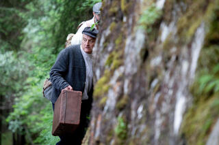 Director, actor and author of the theater group Teatro Caprile, Andreas Kosek reenacts an emigration scene on the old Roman road in the Krimmler Tauern Alps on the border between Austria and Italy