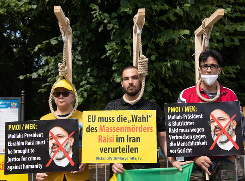 Demonstrators pose with mock-ups of gallows as they take part in a protest called by the National Council of Resistance of Iran (NCRI) against the Iranian regime in front of the Brandenburg Gate in Berlin on July 10, 2021