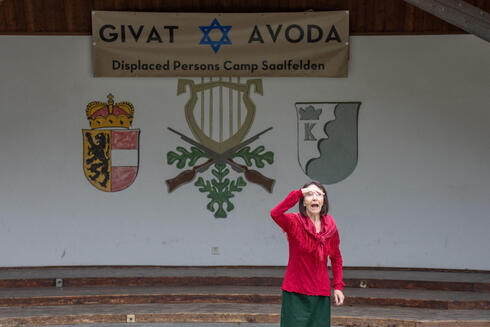 """An actress of the theater group Teatro Caprile gestures during a scene as she stands in front of a banner reading """"Givat Avoda"""", which translates to """"Hill of Labour"""", in the Krimmler Tauern Alps"""