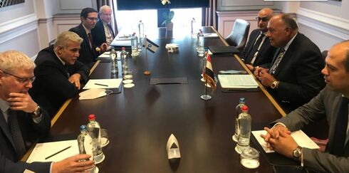 Foreign Minister Yair Lapid, left, meets with Egyptian counterpart Sameh Shoukry in Brussels, July 11, 2021