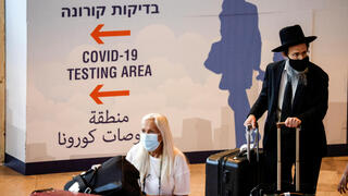 Travellers carry their luggage in the arrivals terminal at Israel's Ben Gurion International Airport, amid a spread of the Delta variant