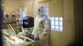 Hospital staff provide medical care for patients at a coronavirus disease (COVID-19) ward amid a surge in new cases