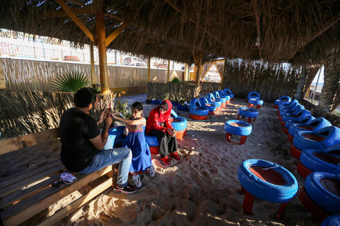 Palestinian beachgoers sit on chairs that have been made of car tires at an environment-friendly beachfront cafe in Gaza July 8, 2021
