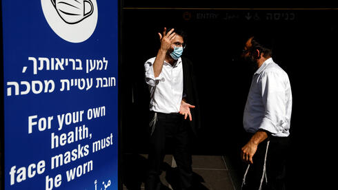 Men stand next to an information banner at Israel's Ben Gurion International Airport, amid a spread of the Delta variant of the coronavirus disease (COVID-19), near Tel Aviv