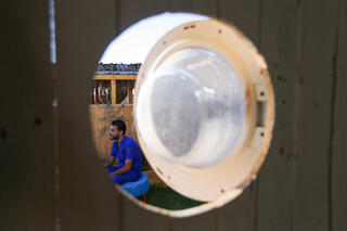 Palestinian artist, Ali Mhana, is seen through a glass door of a washing machine that he used as a window of his makeshift office at an environment-friendly beachfront cafe in Gaza, July 8, 2021
