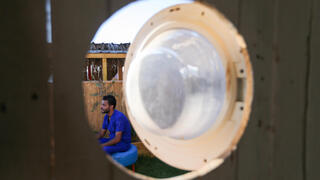 Palestinian artist, Ali Mhana, is seen through a glass door of a washing machine that he used as a window of a his makeshift office at an environment-friendly beachfront cafe in Gaza, July 8, 2021
