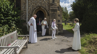 The Rev. Jonathan Gordon, left, and Assistant Vicar Miranda Sheldon, right, greet Anglican worshippers at St. Mary's Church, Northchurch in Berkhamsted, England
