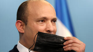 Prime Minister Naftali Bennett holds a face mask during a press conference regarding the COVID-19 situation in Israel