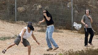 Israeli settlers throw stones at Palestinian houses (not seen) in the West Bank city of Hebron