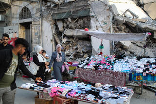 A Palestinian sells socks on a stall near the rubble of his old Gaza City store that was destroyed in an Israeli airstrike in May