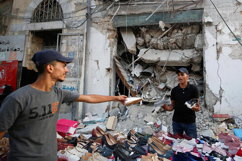 A Palestinian sells shoes on a stall near the rubble of his old shoe store that has been destroyed in an Israeli air strike, ahead of Eid Al-Adha Muslim holiday, in Gaza City
