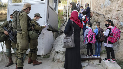 Palestinian students and teachers wait for Israeli soldiers to allow them to cross a military checkpoint near the Jewish settlement of Beit Hadasa in the occupied West Bank city of Hebron