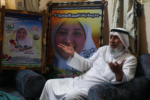Palestinian grandfather, Mahmoud Issa, who lost a daughter and grandchild, in an Israeli bombing in May fighting, sits at his home, in the central Gaza Strip