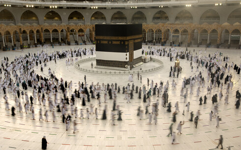 Muslim pilgrims circumambulate the Kaaba, the cubic building at the Grand Mosque, as they wear masks and keep social distancing, a day before the annual hajj pilgrimage