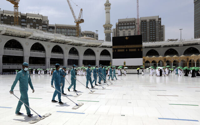Workers disinfect the grounds as Muslim pilgrims circumambulate around the Kaaba