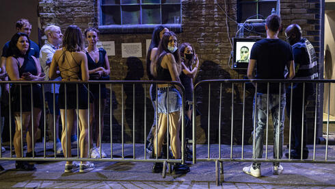 People line up in England to enter clubs after the curbs are lifted