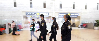 Police officers wearing face masks enforce coronavirus health guidelines at Ben Gurion Airport