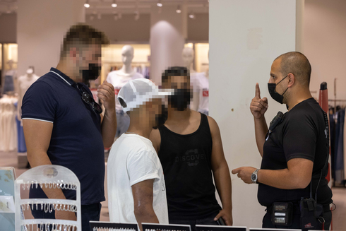 An inspector instructs visitors to a mall in Rishon Lezion on how to correctly wear their face masks (Photo: Tal Shahar)