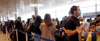 Travelers donning face mask standing in queue at Ben Gurion Airport