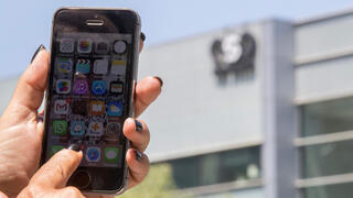 IPhone held in front of NSO building
