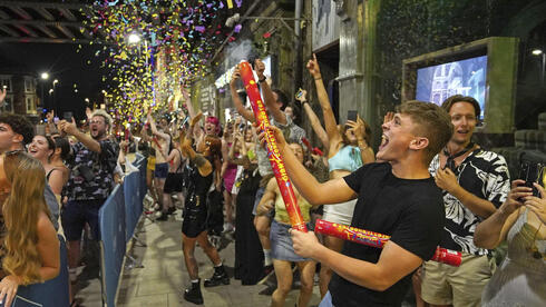 Partygoers celebrate lifting of curbs at midnight