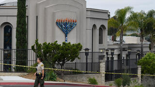a San Diego county sheriff's deputy stands in front of the Chabad of Poway synagogue, in Poway, Calif.
