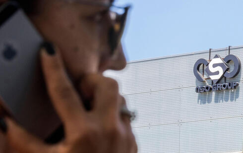 Israeli woman uses her iPhone in front of the building housing the Israeli NSO group, in Herzliya, near Tel Aviv