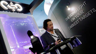 A man reads at a stand of the NSO Group Technologies at the annual European Police Congress in Berlin