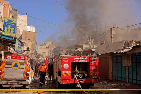 Palestinian rescuers and firefighters gather at the scene of a blast in Gaza City