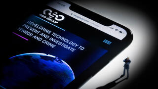 This studio photographic illustration shows a smartphone with the website of Israel's NSO Group which features 'Pegasus' spyware, on display in Paris on July 21, 2021