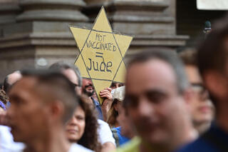 Anti-health pass protestor in Paris holding a yellow Star of David