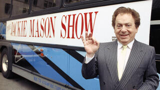 Actor/comedian Jackie Mason  stands beside a bus displaying a sign advertising his TV show,