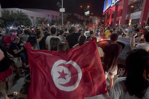 People celebrate in the street after Tunisian President Kais Saied announced the dissolution of parliament and Prime Minister Hichem Mechichi's government in Tunis