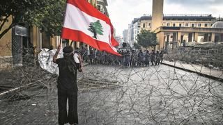 A protestor holding a Lebanese flag demonstrates over Lebanon's economic meltdown and political crisis in Tripoli