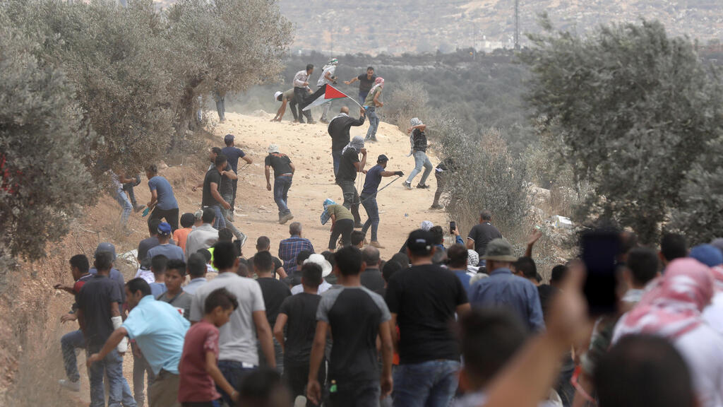 Palestinian protesters throw stones at Israeli troops during clashes after a demonstration against the expansion of the new Jewish outpost of Eviatar on the lands of Beita village