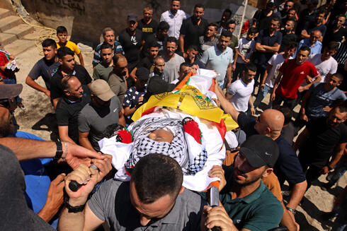 Mourners carry the body of Palestinian boy Mohamad al-alami during his funeral in the town of Beit Omar