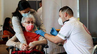 An elderly woman receives a booster shot of her vaccination against the coronavirus disease (COVID-19) at an assisted living facility, in Netanya, Israel January 19, 2021