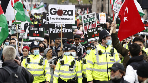 Protesters hold placards and banners in London, Saturday, May 22, 2021, as they take part in a rally supporting Palestinians