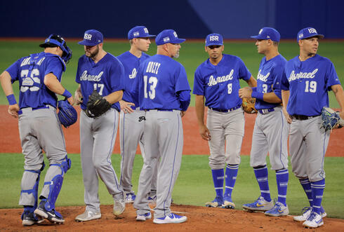 Israel's head coach Peter Kurz (C) talks to his players during the fourth inning of the Tokyo 2020 Olympics